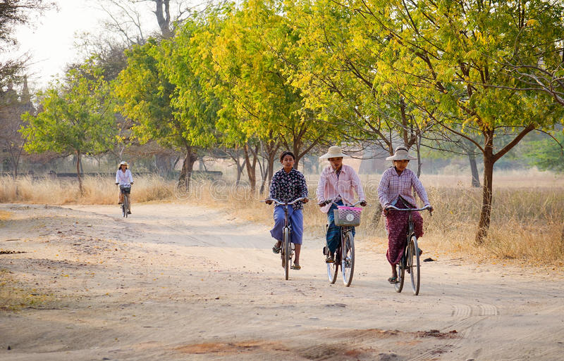 Burmese women biking on rural road in Inlay, Myanmar.  royalty free stock images