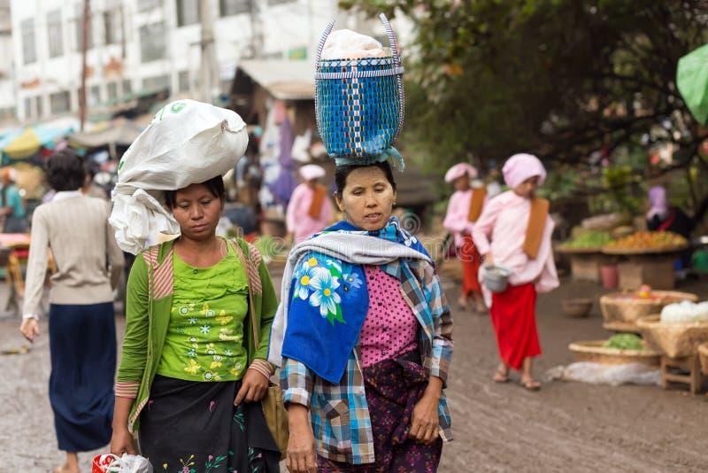 Burmese women carrying bag on head royalty free stock image