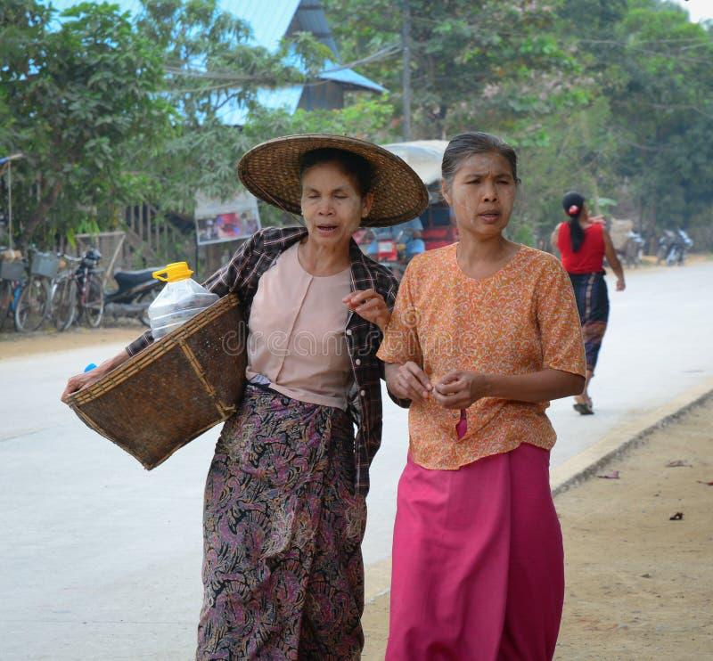 Burmese women carrying a heavy basket royalty free stock image