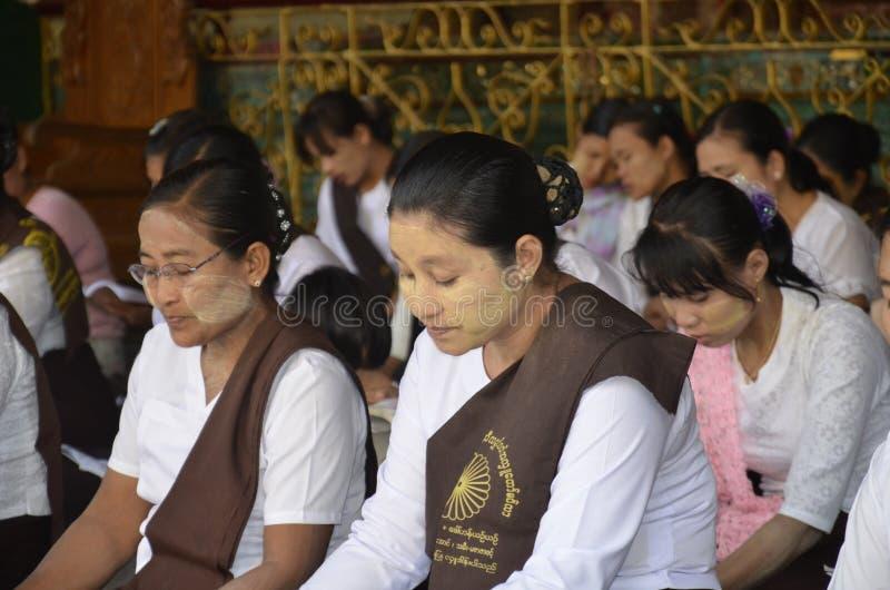 Burmese women chanting evening prayers. royalty free stock images