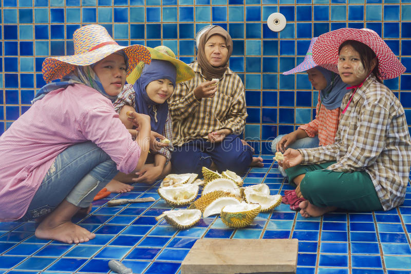 Burmse workers eating a durian royalty free stock photo