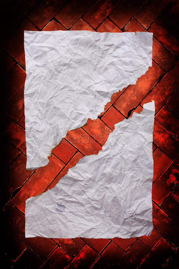 Burn creased paper on red brick wall