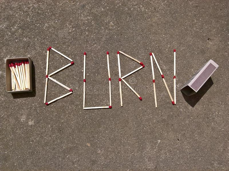 Burn Lettering and the Match Box. `Burn` writing made of matches. Matchbox on the concrete pathwalk. Bright matchsticks with red heads stock photos