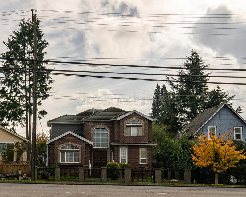 BURNABY, CANADA - October 24, 2018: House in residential area with yellow and red trees in autumn. BURNABY, CANADA - October 24, 2018: House in residential area royalty free stock photography