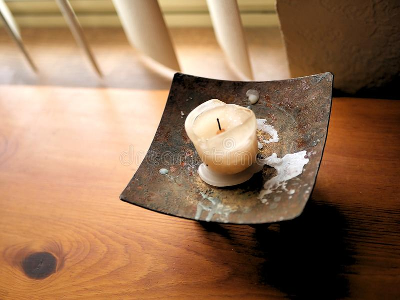Melted Candle Wax on Vintage Metal Holder on Wood Desk. A burned candle with melted wax dripping on the metal holder, sitting in natural light near a window stock photo