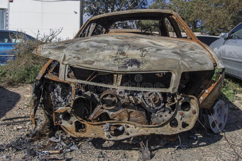 Burned car, destroyed vehicle after a fire melted is on the street stock photo