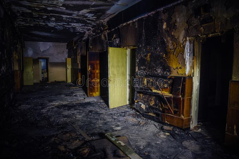 Burned by fire interior of old hospital. Charred walls and doors of corridor.  stock photos