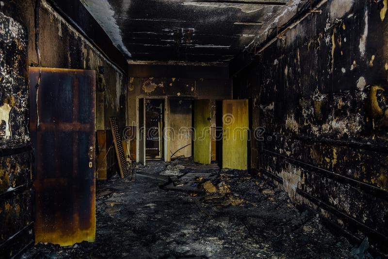 Burned by fire interior of old hospital. Charred walls and doors of corridor.  stock images