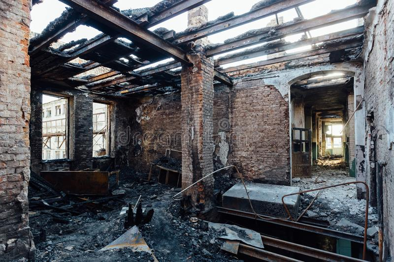 Burned interiors after fire in industrial or office building. Burnt furniture, failed roof stock image