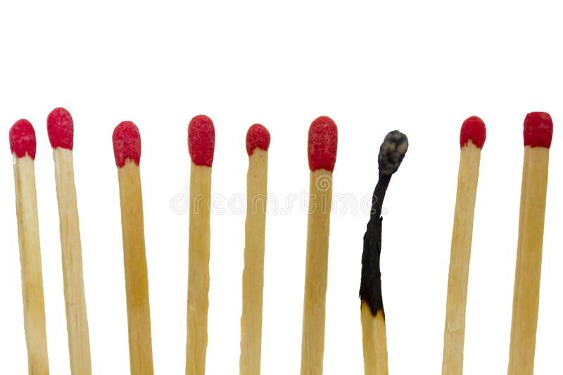 Burned match next to new matches. Against white background royalty free stock photography