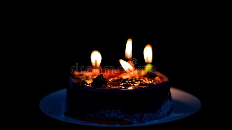 Burned out candles on b-day cake, transience of life concept, black background. Stock photo royalty free stock image