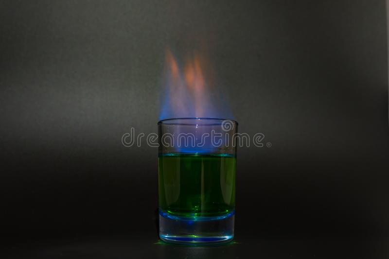 Burning absinthe in a glass on a black background. 2018 royalty free stock images