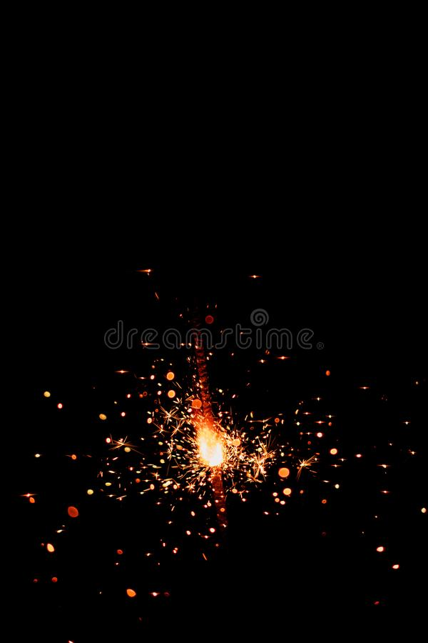 Burning bengal light sparkler on a dark black background.  stock image