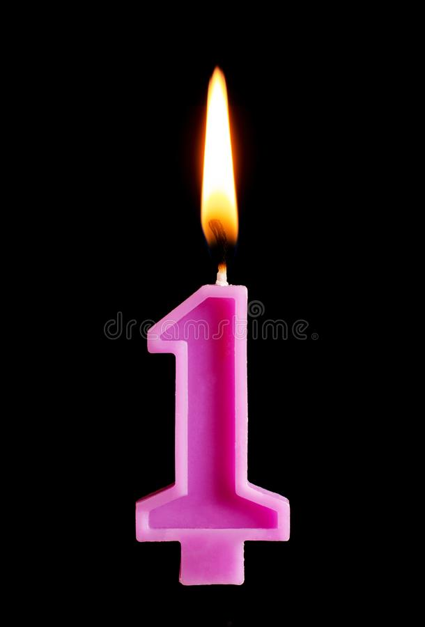 Burning birthday candle in the form of 1 one figures for cake isolated on black background. The concept of celebrating a birthday, royalty free stock photos