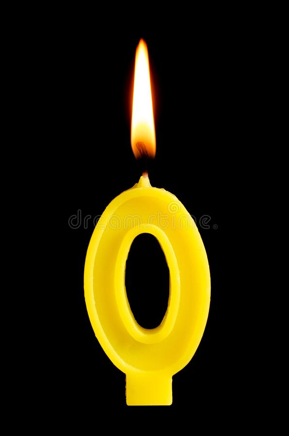 Burning birthday candle in the form of 0 zero figures for cake isolated on black background. The concept of celebrating a birthday stock photos