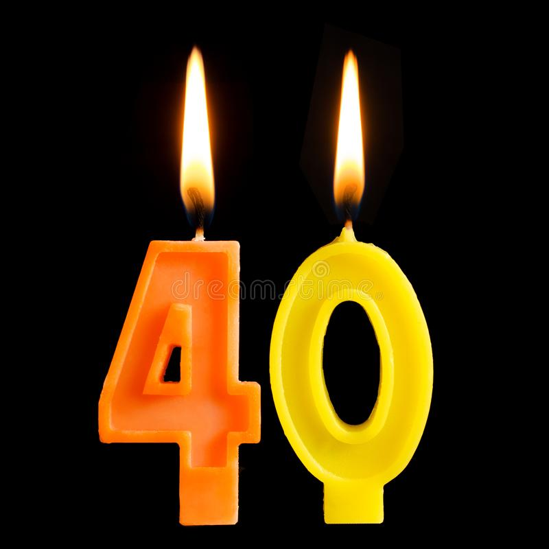 Burning birthday candles in the form of 40 forty figures for cake isolated on black background. The concept of celebrating a birth royalty free stock images