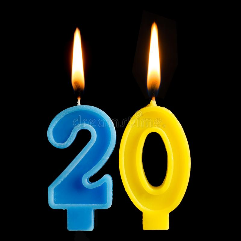 Burning birthday candles in the form of 20 twenty figures for cake isolated on black background. The concept of celebrating a birt. Hday, anniversary, important royalty free stock images