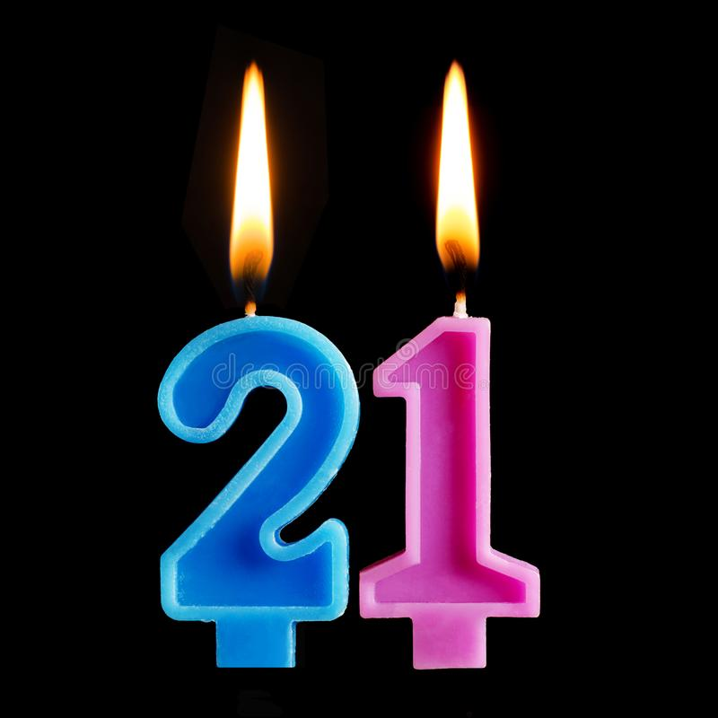 Burning birthday candles in the form of 21 twenty one for cake isolated on black background. The concept of celebrating a birthday stock photos