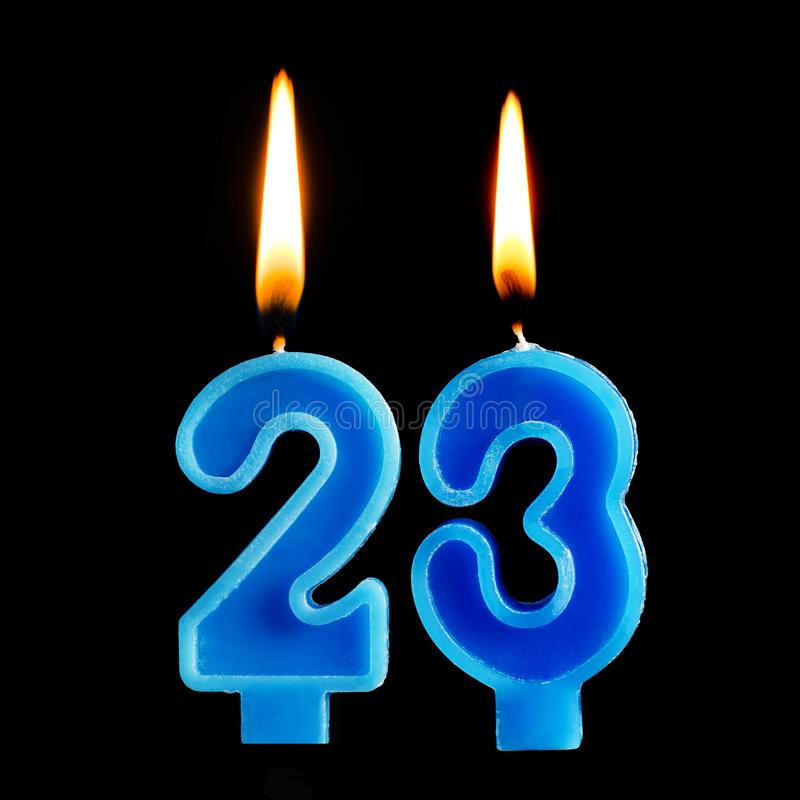 Burning birthday candles in the form of 23 twenty three for cake isolated on black background. The concept of celebrating a birthd royalty free stock photo