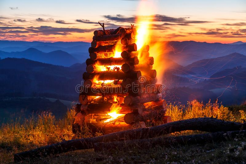 The burning of bonfire over a mountainous landscape. stock images