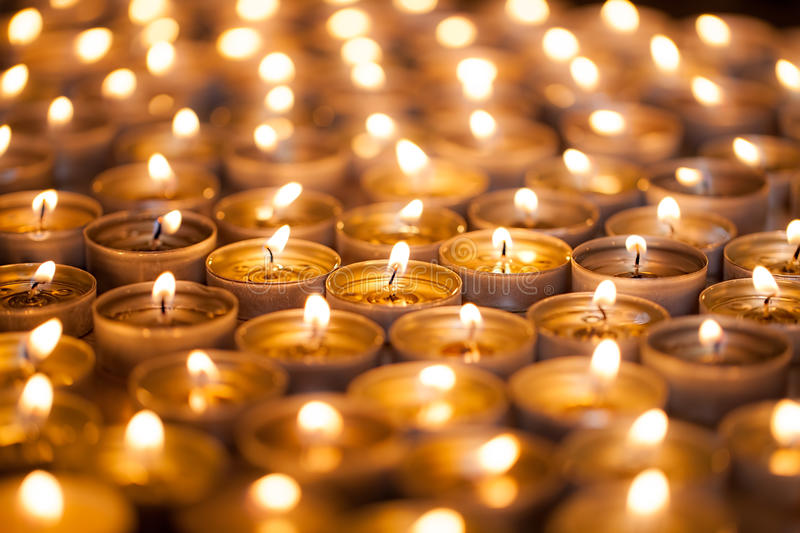 Burning bright. Golden warm glow from candle flames. Many beautiful lit tealight candles glowing. royalty free stock photo