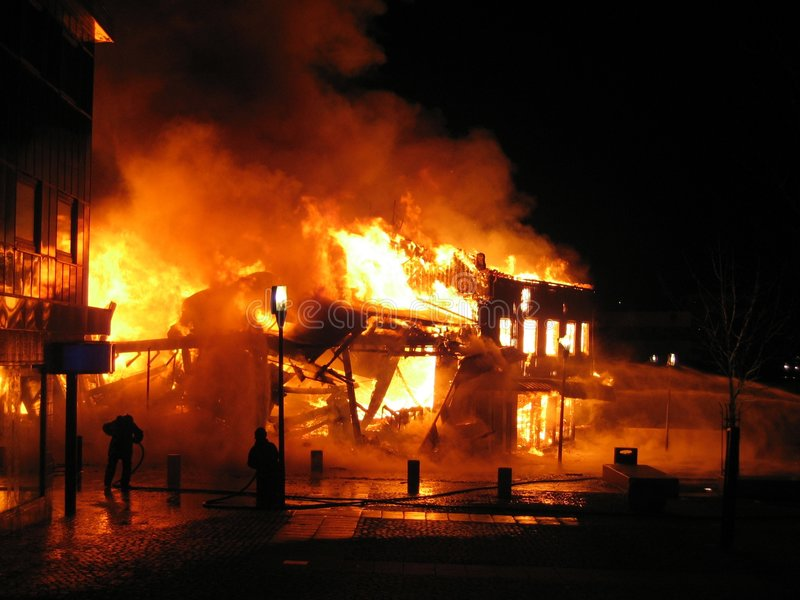 Burning building. Building in a flaming inferno, and two firefighers fighting the flames