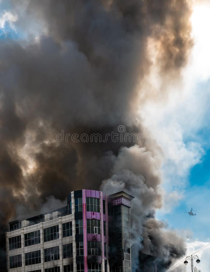 Burning building in thick toxic smoke. Big fire stock photography