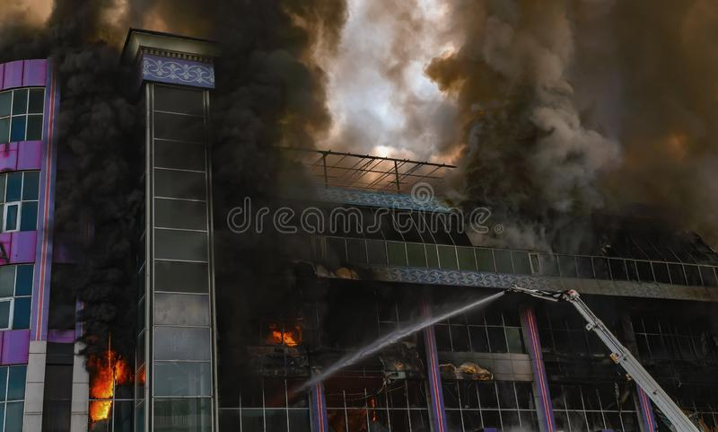 Burning building in thick toxic smoke. Big fire stock image