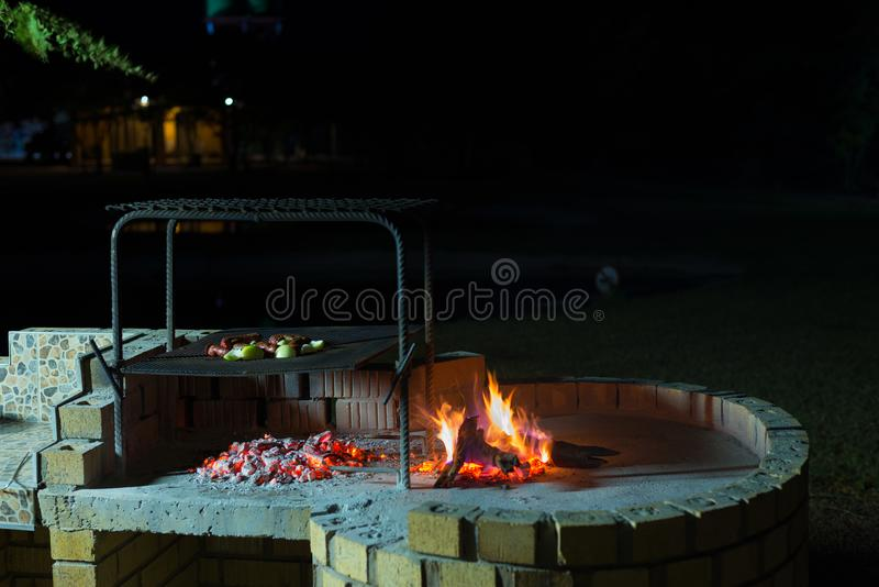 Burning camp fire at dusk in camping site, preparing for barbeque or braai, outdoors activity in South Africa. Selective focus on. Fire and firewood royalty free stock photos