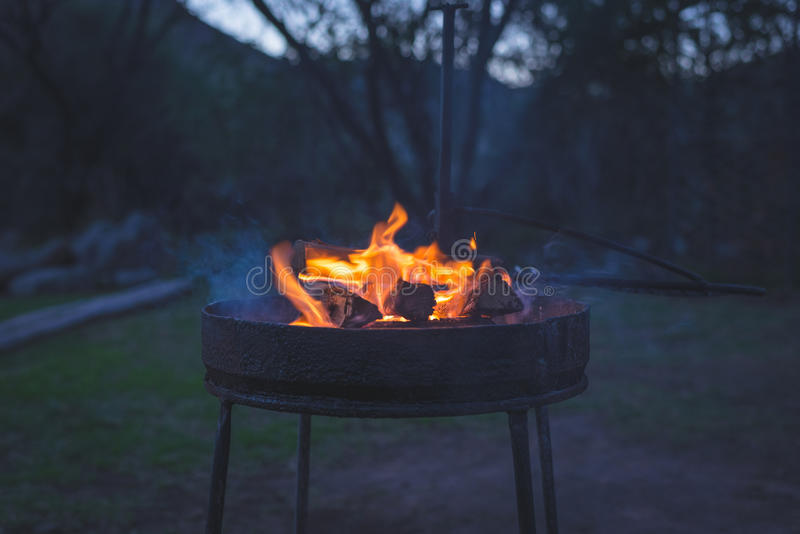 Burning camp fire at dusk in camping site, preparing for barbeque or braai, outdoors activity in South Africa. Selective focus on stock photo