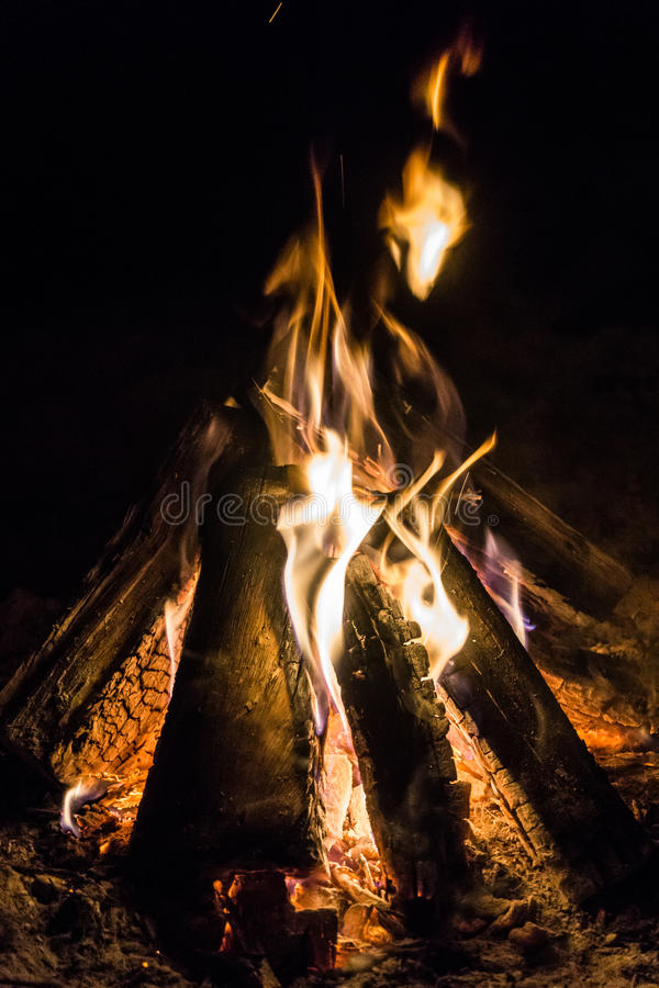 Burning Camp Fire. Camp fire burning, with the wooden logs in a typical triangle teepee position, and flames reaching up into the black sky stock photo