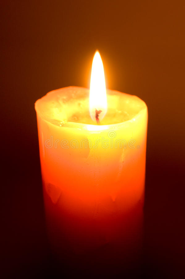 Burning candle. In the dark stock photography