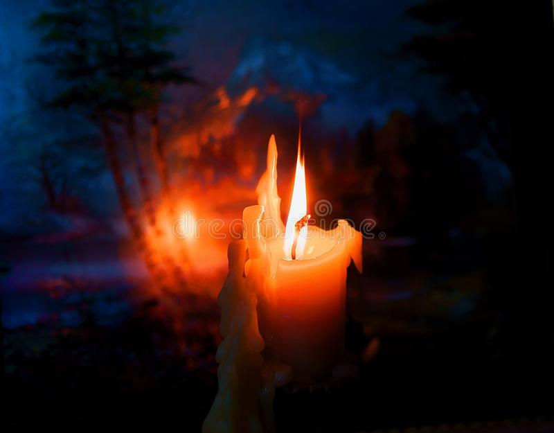 The flame of a burning candle. Burning candle on the background of the painting, flames painting royalty free stock photo