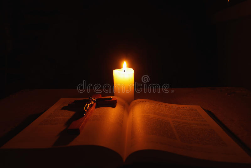 Burning candle, bible and crucifix on desk. In dark stock photography