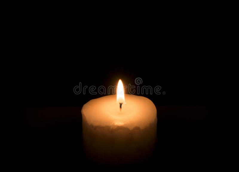 Burning candle. On a black background stock photos