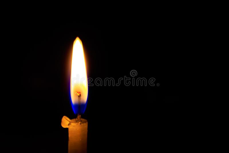 A burning candle on black background, close up. royalty free stock photography
