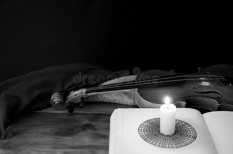 Violin and candle on a table royalty free stock photography