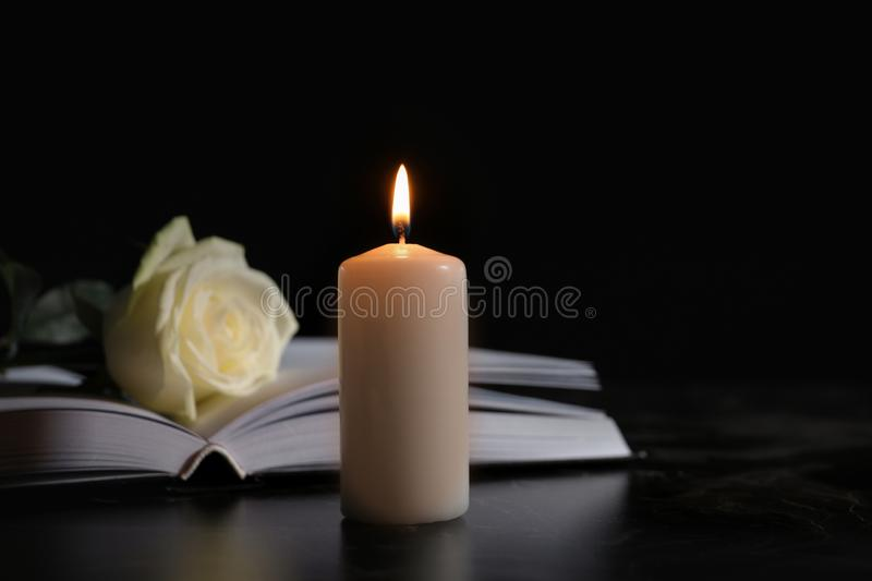 Burning candle, book and white rose on table in darkness, space for text royalty free stock images