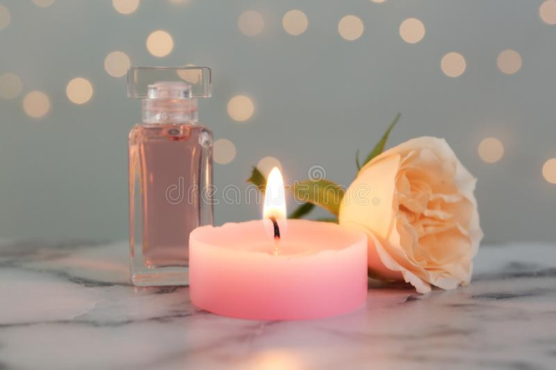 Burning candle, bottle of perfume and rose against blurred lights stock photos