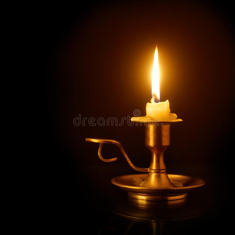 Burning candle on candlestick royalty free stock images