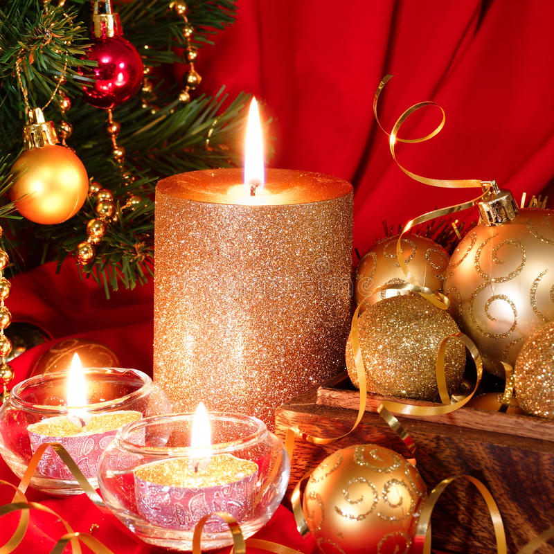Burning candle, Christmas balls and fir tree. Red background. Golden Christmas balls in a wooden box and candle. New Year composition royalty free stock photo