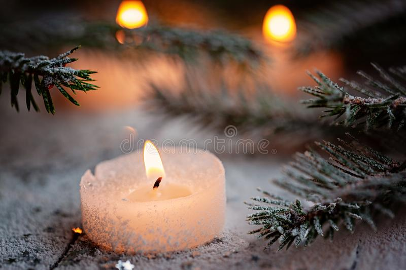 Burning candle and Christmas decoration over snow with pine branches on white wooden background.  royalty free stock images