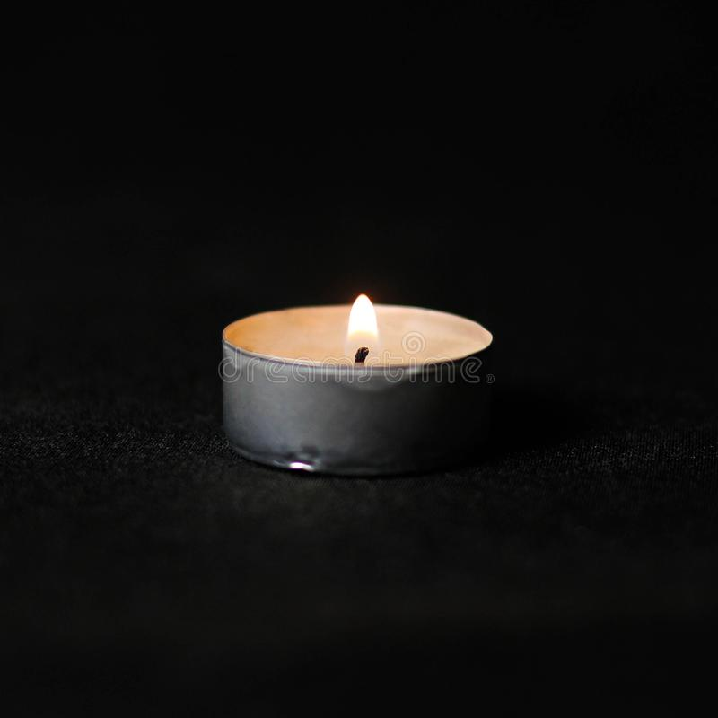 Burning candle. Close up. Isolated on black background royalty free stock image