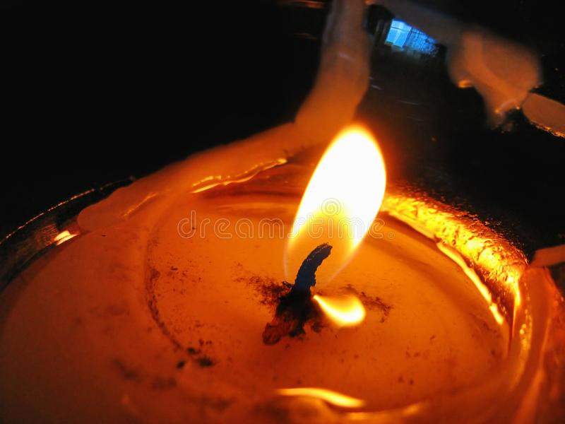 Burning candle closeup. Burning candle flame closeup in the dark stock photography