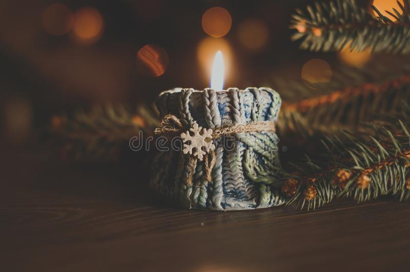 Burning candle in a cozy blue candlestick with a snowflake on th royalty free stock photography