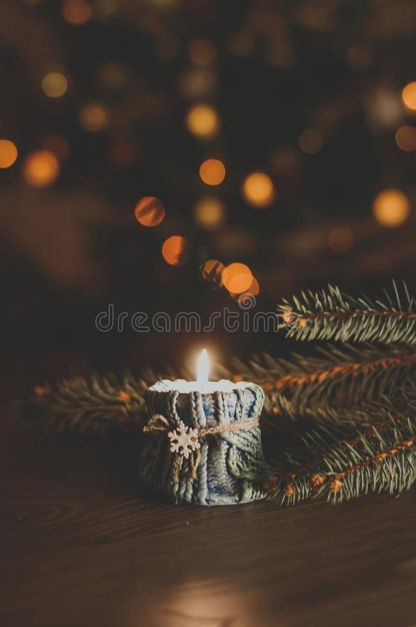 Burning candle in a cozy candlestick with a snowflake on th stock image