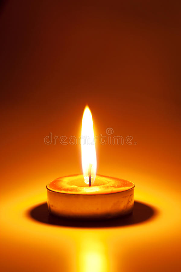 Burning candle. In the dark stock photo