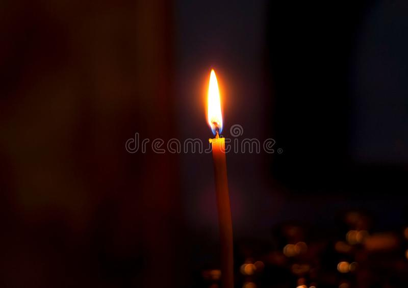 Burning candle on a dark background, closeup, copy space. Burning candle on dark background, closeup, copy space royalty free stock image