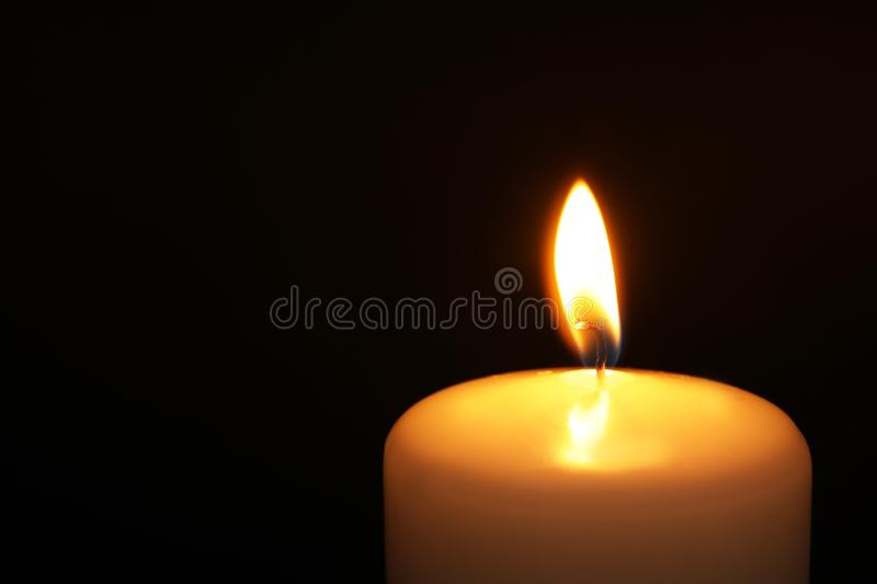Burning candle on dark background, closeup with space for text. Symbol of. Sorrow stock image