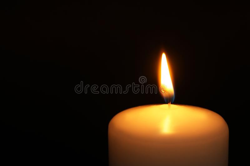 Burning candle on dark background, closeup with space for text. Symbol of. Sorrow royalty free stock image